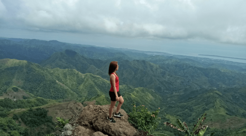 a Filipino girl at the peak of a mountain