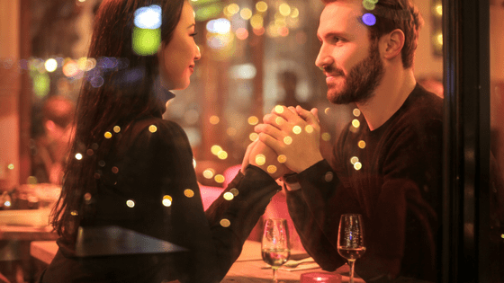 a couple holding hands in a restaurant