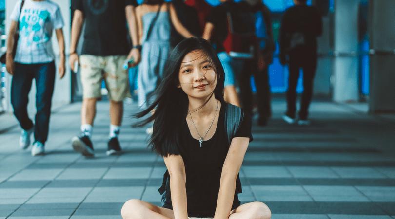 Thai girl sitting on the sidewalk