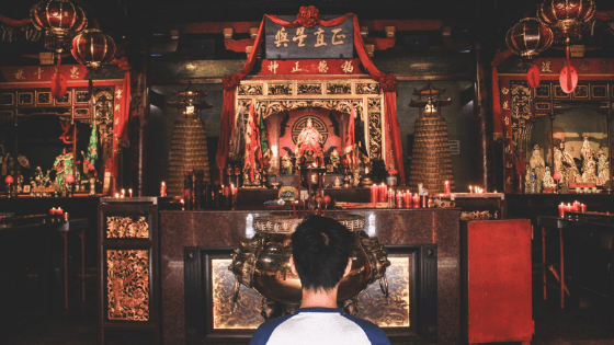 an Indonesian man praying in temple